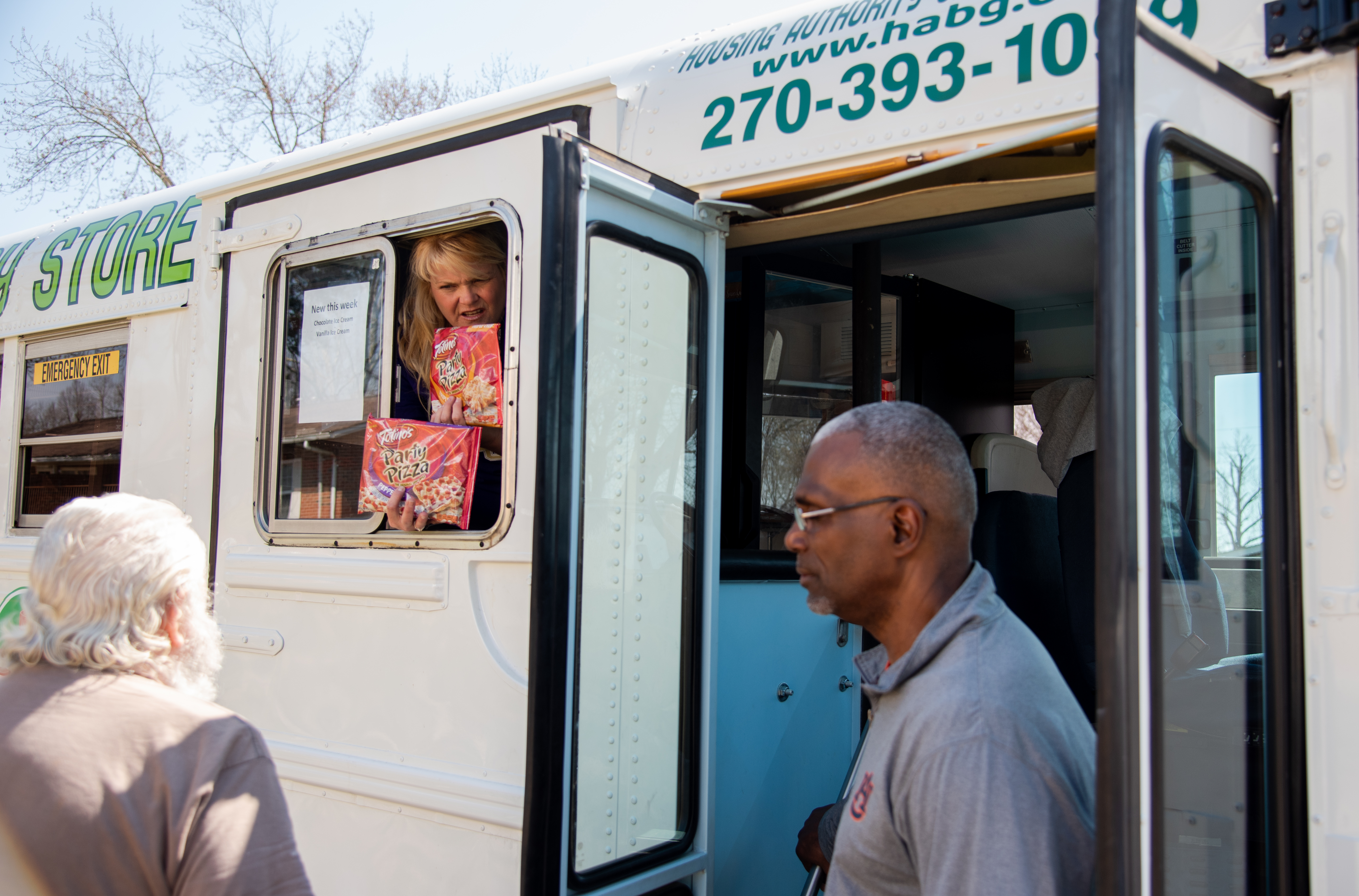 Lori Richey shows Mobile Grocery Bus customers the two kinds of frozen pizza the bus offers, a new edition at that time when the bus was still establishing its customer base in 2019.